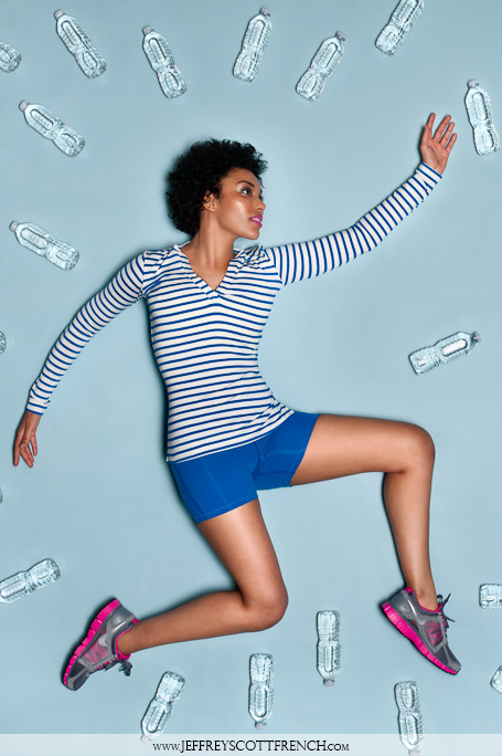 An image of a woman jumping and reaching for water while wearing activewear on a sky blue background by Jeffrey Scott French