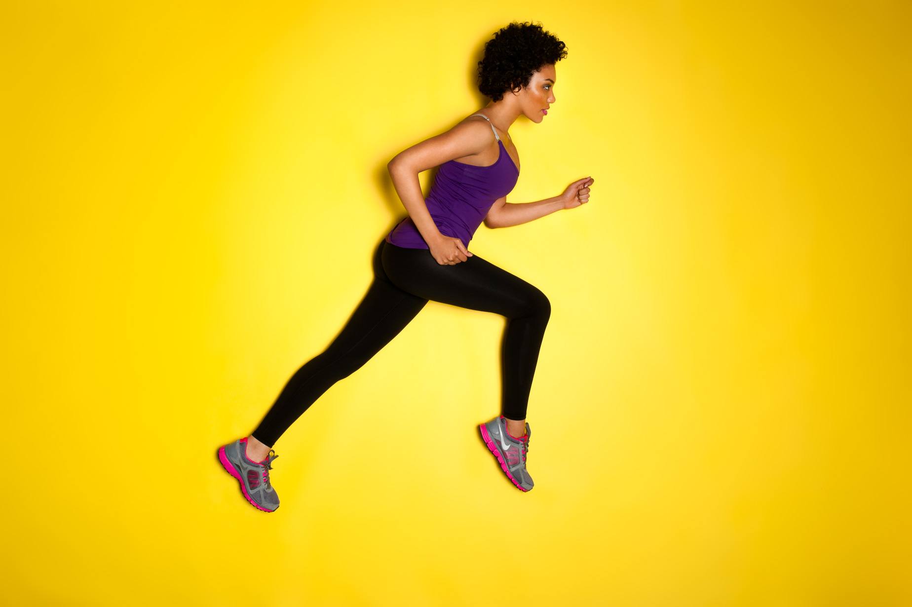 A color image of a woman wearing athletic wear running on a yellow background by Jeffrey Scott French