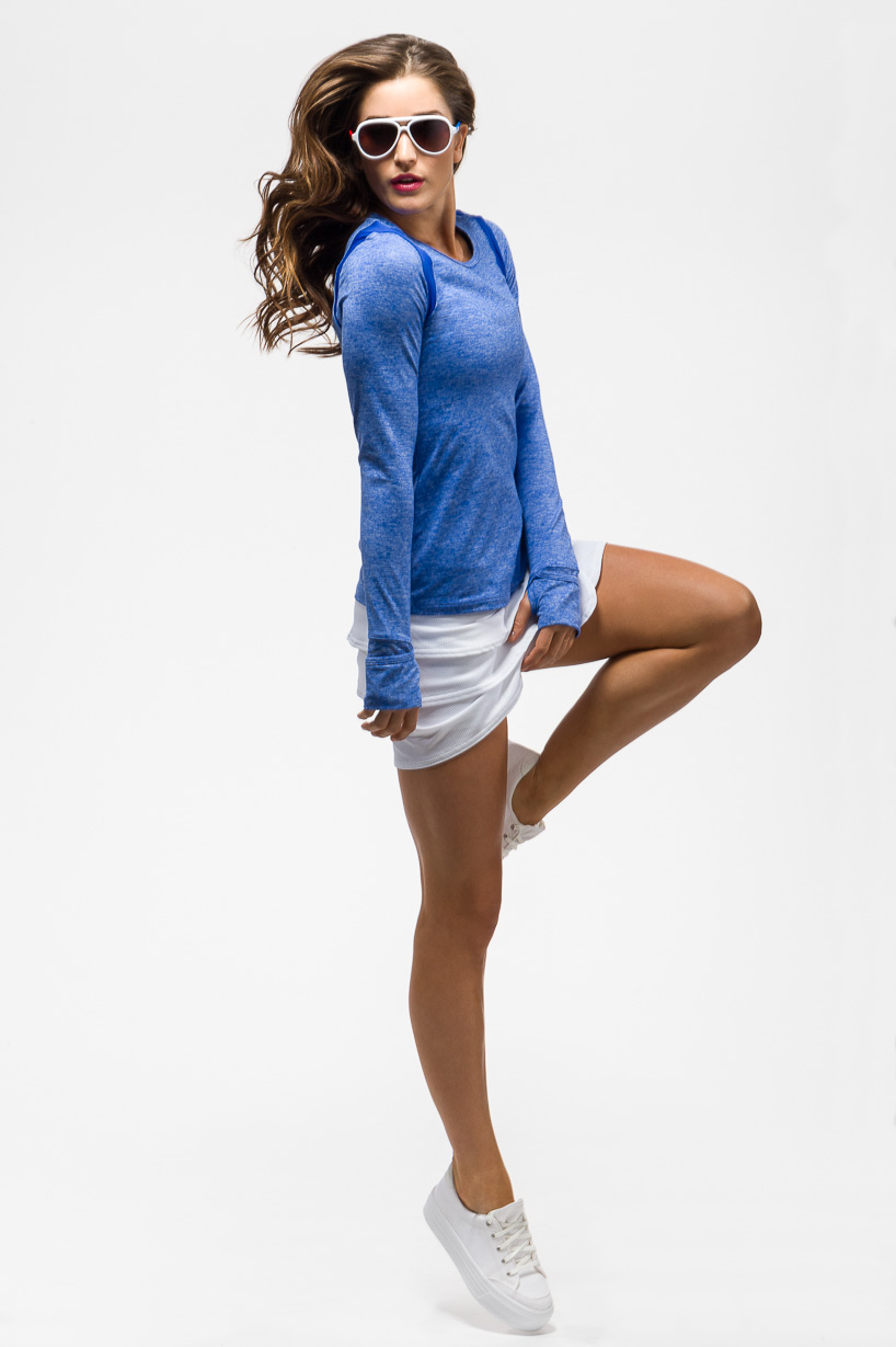 A color image of a woman wearing athletic wear jumping on a white background by Jeffrey Scott French