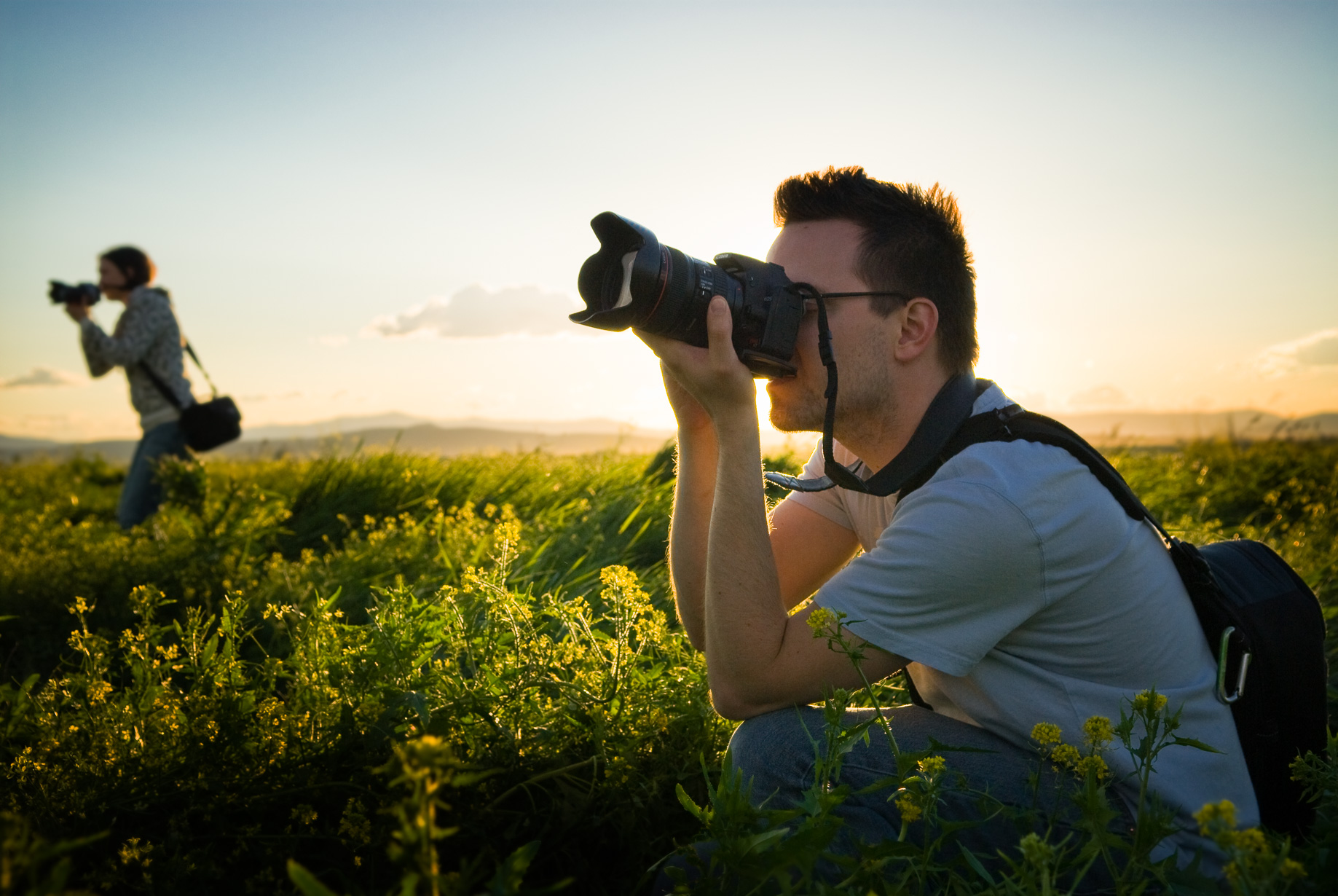 A color image of two photographers in a green field at sunset by Jeffrey Scott French